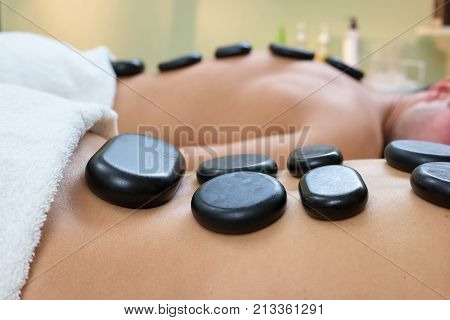 Man and woman getting hot stone massage. Close up of young couple receiving hot stone therapy at beauty spa. Beauty treatment concept.