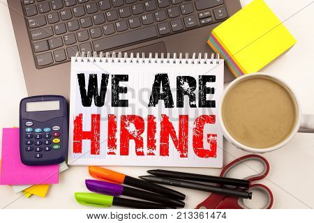 We Are Hiring Writing Text In The Office With Surroundings Such As Laptop, Marker, Pen, Stationery.