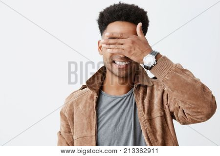 I don't see you. Close up portrait of young attractive dark skinned man with afro hairstyle in casual autumn siling, closing eyes with hand, playing with little child on street.