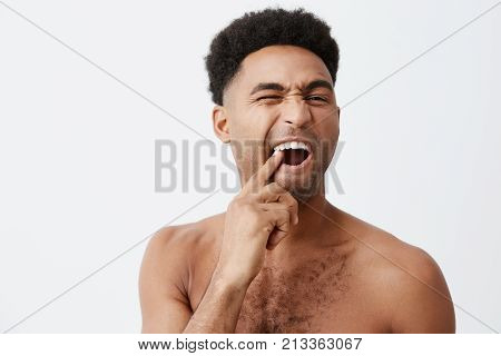 Young funny good-looking afro american male with curly hair without clothes picking in teeth looking at mirror with mean expression taking bath in morning