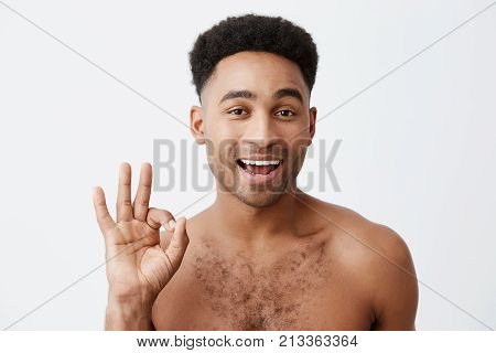 It OK. Don't worry. Close up of cheerful young attractive dark-skinned man with afro hairstyle with naked torso showing OK sign with hand, winking, looking in camera with flirty expression