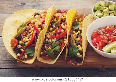 Three Mexican tacos with minced beef and mix vegetables on old rustic table. Mexican dish with sauce salsa in bowl and avocado. Spicy and hot street food. Close-up.