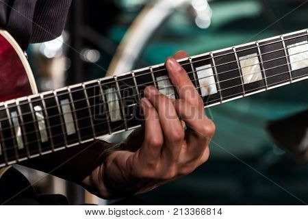 The guitarist clamped the chord on the electric guitar fretboard.
