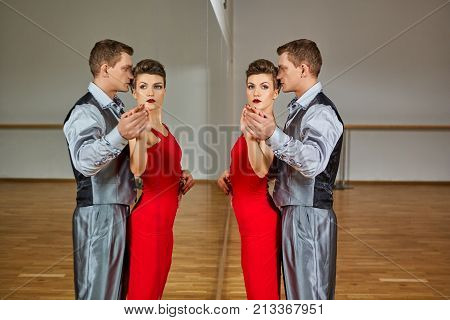 beautiful couple dancing tango. young woman in red dress and man in suit practicing in dancing studio mirror room. copy space.