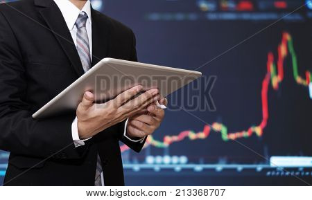 Businessman working on digital tablet with raising financial, stock exchange graph background. Investment in stock exchange and forex trading