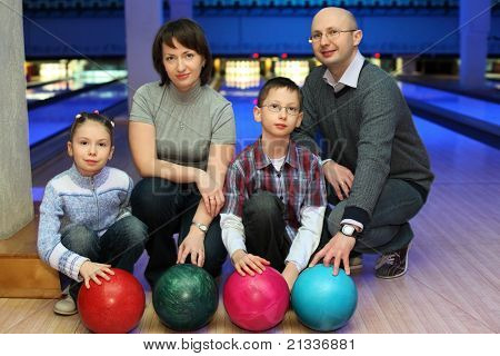 Family from four persons  of squatting in club for bowling and holds on to balls, focus on children and balls poster