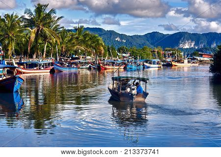 A local fisherman goes out on a boat from boats park to the sea for fishing. Traditional colorful asian fishing boats in fishing village. Langkawi island Malaysia.