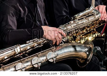 A saxophonist man put a baritone saxophone on his knees and waits for the orchestra's performances. Close-up.