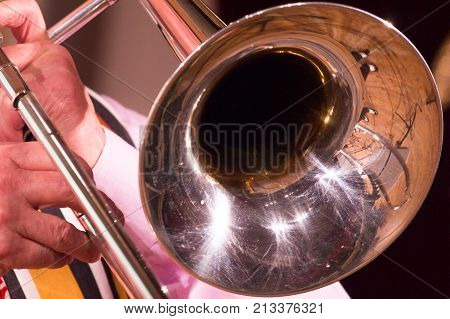 A man on a trombone plays jazz or other music. close-up
