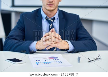 Mid-section portrait of unrecognizable business analyst sitting at desk in office with hands clasped looking at data graph