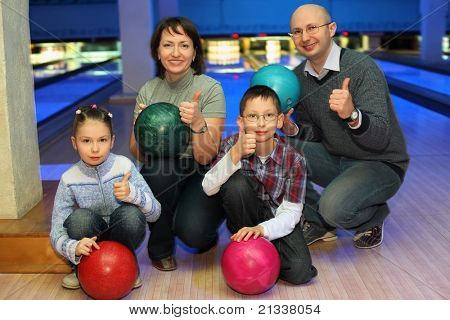 Family of squatting in bowling club and shows  hands of ok, focus on children