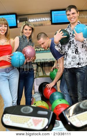 Two girls and two youths stand near tenpin bowling with balls for playing bowling and smile, focus on girl and fellow on sides