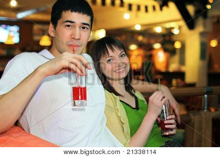 Man and girl sit on bench and drink cocktail, focus on man