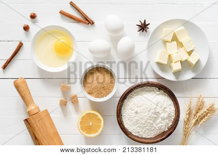 Baking ingredients flour, wheat, eggs, spices, eggs, butter and sugar on old white table. Top view. Baking, cake or cookie recipe preparation