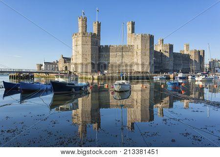 Castle and moored boats at harbor of Caernarfon, North Wales