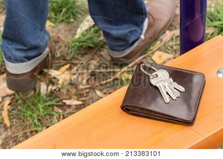 A man lost his keys and a purse with money. The men leave and only the legs and shoes are not in focus and the keys and wallet on the scroll