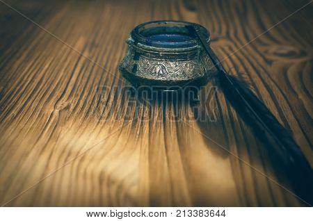 Feather pen and inkwell isolated on wooden table background. Education background.