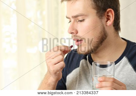 Serious Man Taking A Pill At Home