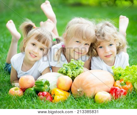 Group of happy children with fruits and vegetables lying on green grass outdoors in spring park. Family picnic. Healthy eating concept