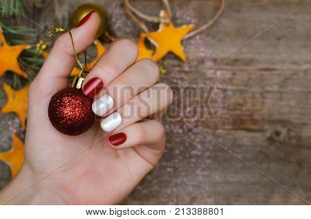 Beautiful female hand with red and white nail design. Christmas nail art.