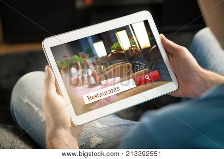 Man using tablet trying to find the perfect restaurant from review website or application. Tavern cafe or bistro search engine and app online. Rating social media on internet.