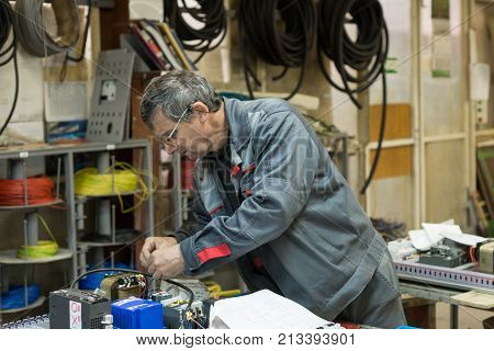 LIPETSK, RUSSIA - JUNE 15, 2017: Lipetsk Machine Tool Plant. The electrician assembles and adjusts the electrical control panel. Works on assembling the electrical circuit of a metal-cutting machine.