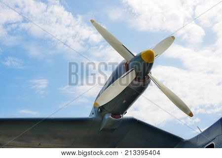 Close up of airplane turboprop engine with propeller parts of aircraft fuselage wings on a sky background