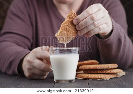 Dunk Sesame Cookies Biscuits In Milk Cup On Table
