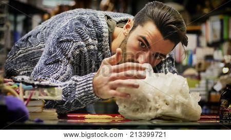 Handsome young man standing near shelf in shop and looking at big mineral stone., namely a quarz crystal