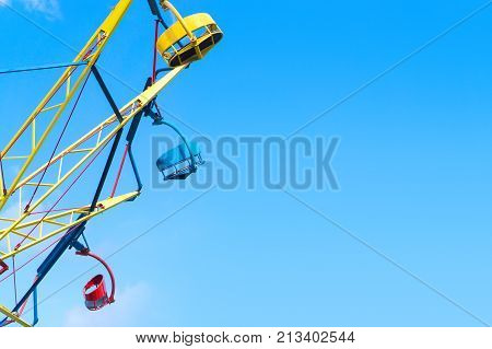 Amusement park background template with negative copy space. Colorful theme park ride against clear blue sky in summer.