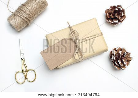 Christmas festive styled stock image composition. Handmade gift box with craft paper gift tag, pinecones, golden scissors, rope and wooden stars on white wooden background, top view.