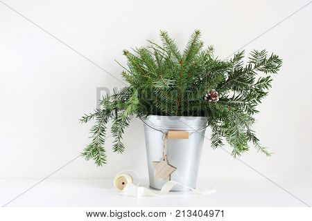 Green fir branches in metalic bucket. Christmas composition with pinecones, wooden star and spool of ribbon lying on white table, holiday still life, winter background.