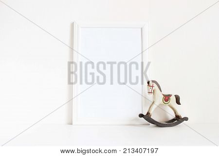 White blank wooden frame mockup with old wooden horse toy on the white table. Styled stock feminine photography. Home decor, Christmas winter concept.