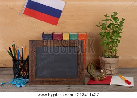 Concept of learning the russian language - blank blackboard flag of the Russian Federation books pencils compass on wooden background
