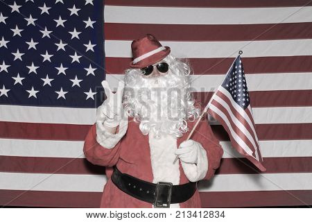 Santa Claus poses in front of an American Flag.  Santa Claus Waves an American Flag as he supports our troops.
