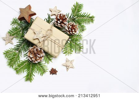 Christmas festive styled stock image composition. Handmade craft paper gift box, pine cones, wooden and anise stars and fir tree branches on white wooden background, flat lay, top view.