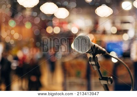 Microphone on a stand ready for live music performance or karaoke night with soft bokeh lights and people silhouettes in the background. Concept for musical singing event, having a good time.