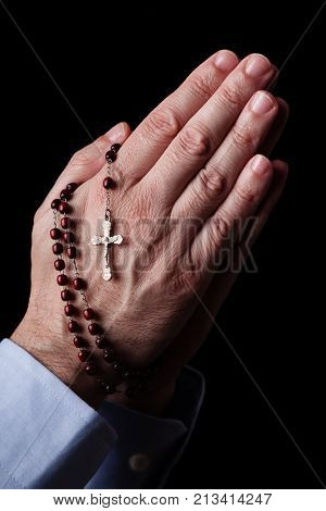 Male hands praying holding a rosary with Jesus Christ in the cross or Crucifix on black background. Mature man with Christian Catholic religious faith