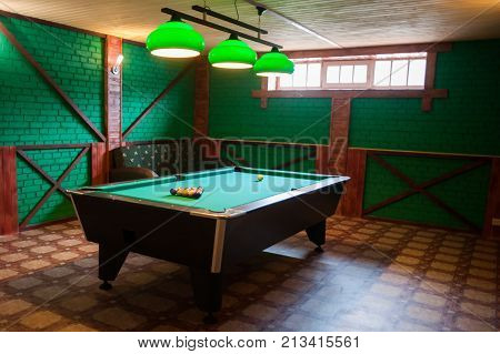 A pool table with balls in a stylized billiard green room