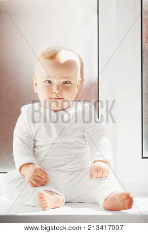 Adorable baby with very serious face expression and light eyes dressed in white crawlers sits on windowsill full of light in confident pose.