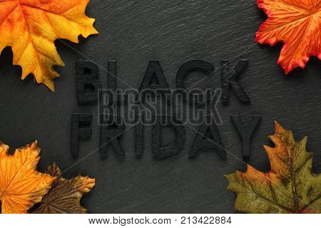 Black Friday text with autumn leaves on black slate background