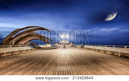 Monster octopus attacking the seaside pier at night coming up from the sea. Moon and stars with a blue sky. Digital fantasy artwork.