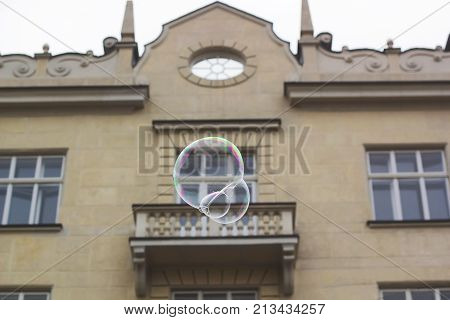 Big soap bubble flies through air in city against old-fashioned house