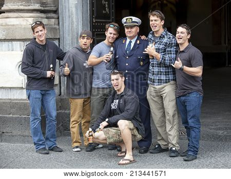 CATANIA, ITALY. April 3, 2015: American group tourists taking picture with an Italian cop. Catania, Sicily in Italy.  Tourists are all happy and amused.