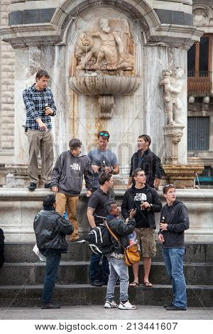 CATANIA, ITALY. April 3, 2015: A group of American tourists is under a monument in the center of Catania in Sicily, Italy. Near them some street vendor.