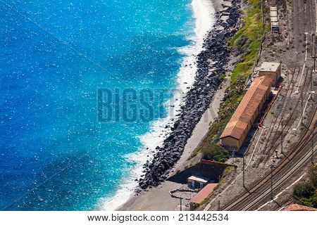 Railway station of Giardini Naxos, Sicily (Italy) and Mediterranean Sea. Aerial view. Visible rail tracks and the lovely blue sea. Place where the photo was taken: Taormina