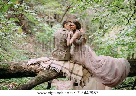 Romantic couple is gently hugs on the log. Autumn wedding Back view