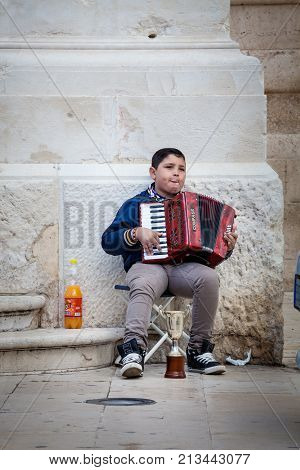 SYRACUSE, ITALY. April 3, 2015: Accordion player, poor child busker in the street in the center of Syracuse in Italy, Sicily. He asks offers to passersby.