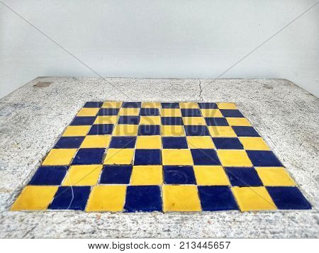 The mosaic blue and yellow chess board built in the mable table in perspective view with white wall background.