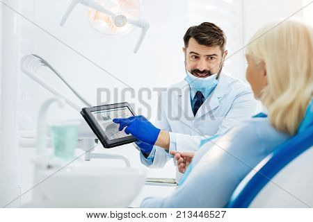 Important facts. Positive dentist using a tablet while talking with a patient and demonstrating useful information